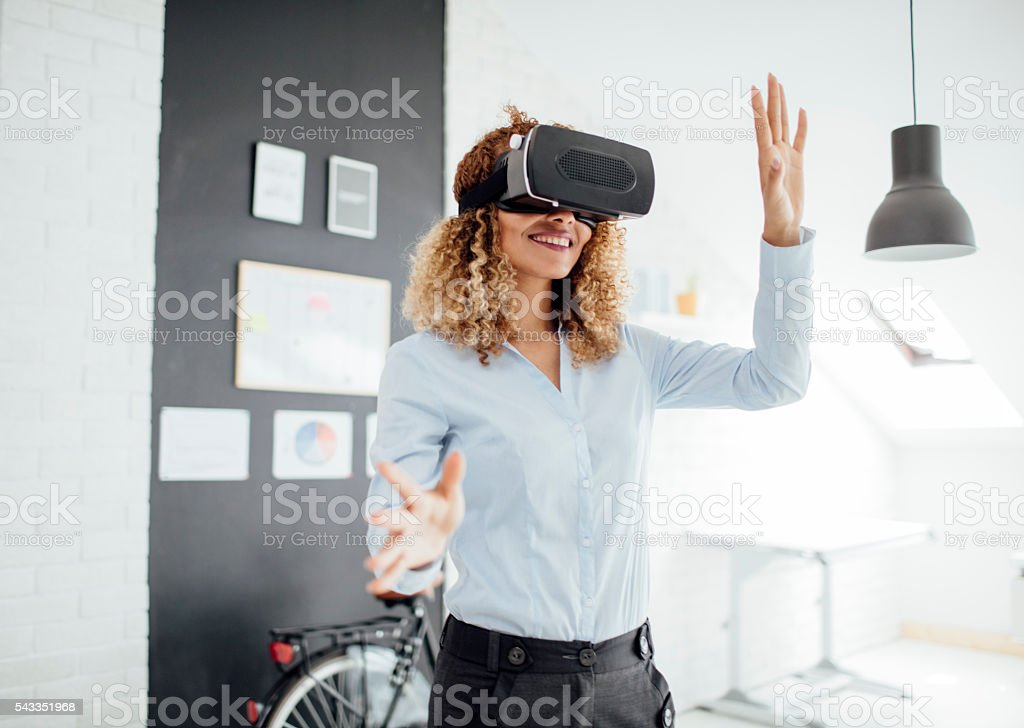 Latina Businesswoman Using Her Virtual Reality Glasses. stock photo