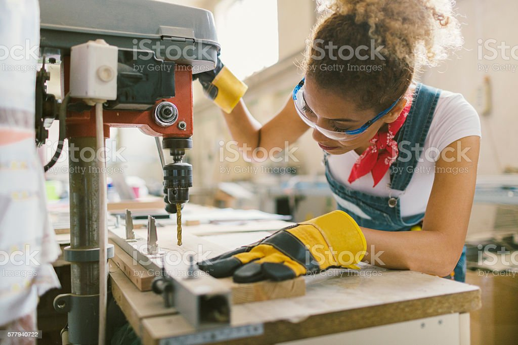 Latina Carpenter Drilling Plank In Her Workshop stock photo