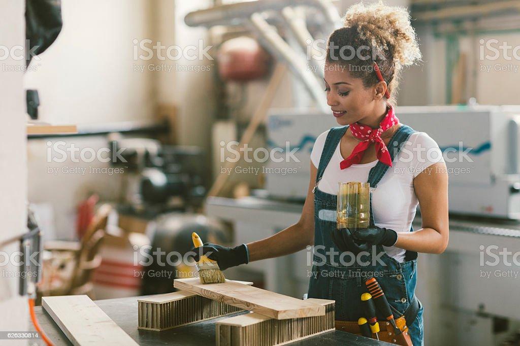 Latina Carpenter Painting Plank. stock photo