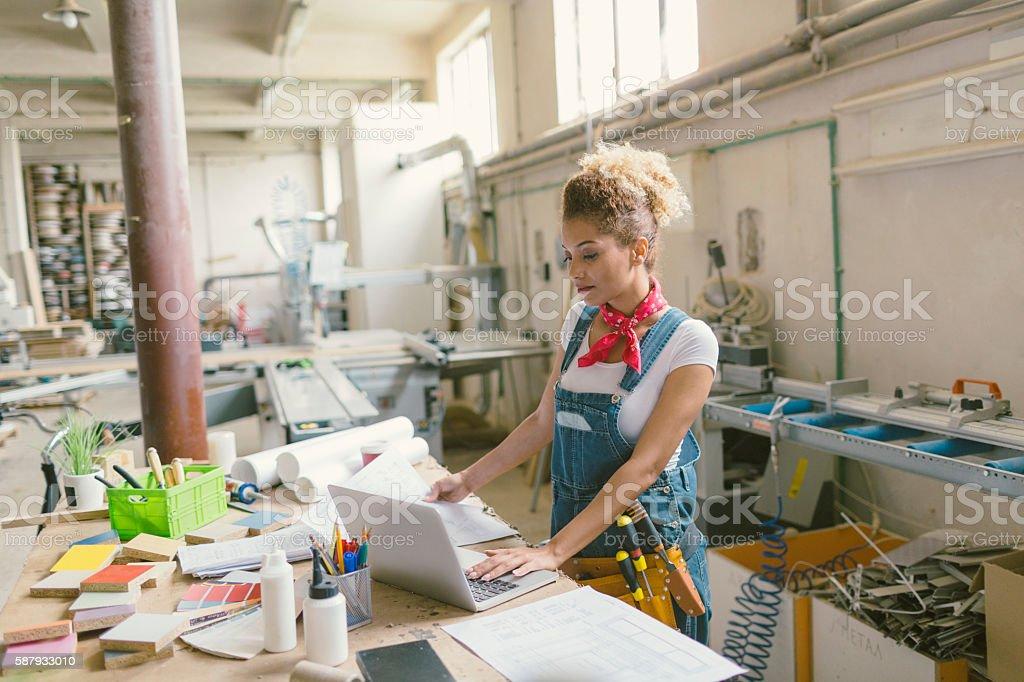 Latina Carpenter Standing In Her Workshop stock photo