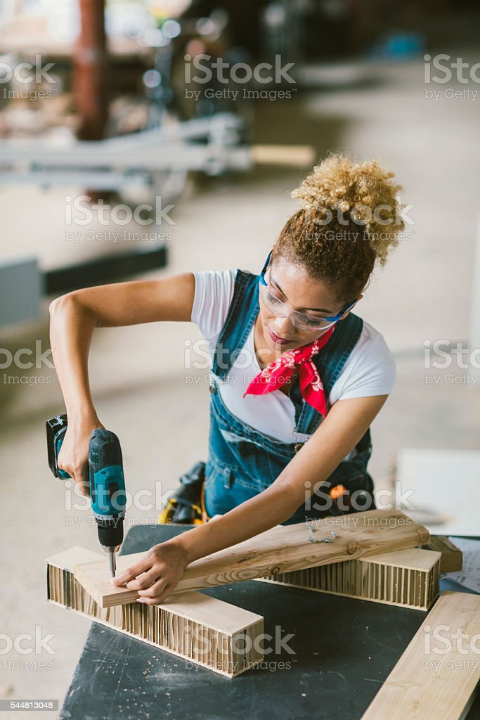 Latina Carpenter Using Electric Screwdriver In Her Workshop stock photo