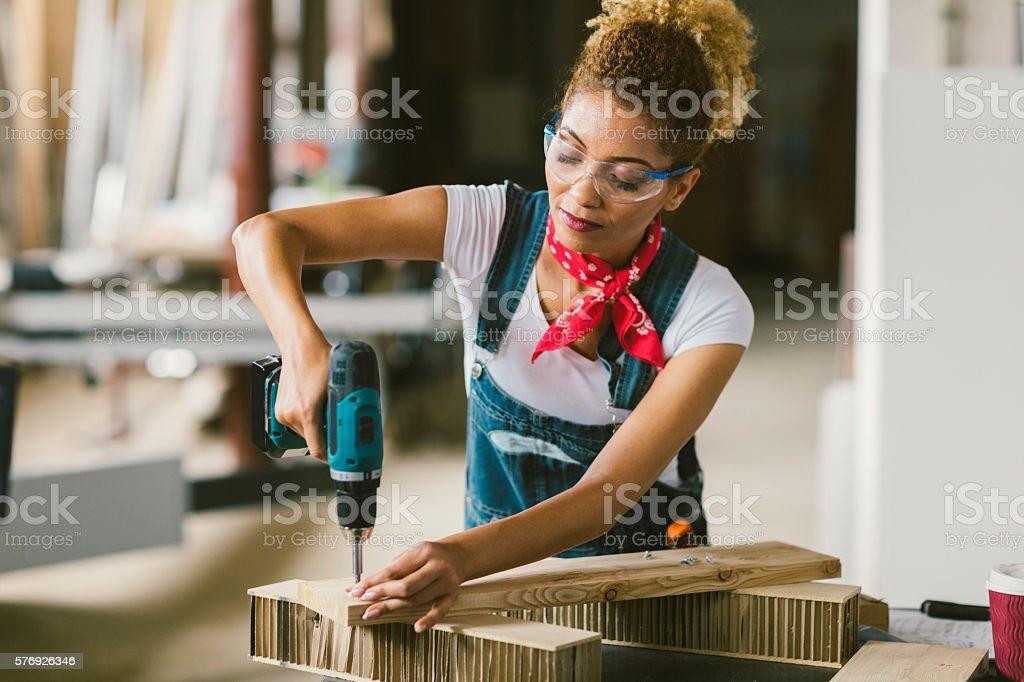 Latina Carpenter Using Electric Screwdriver In Her Workshop stock photo