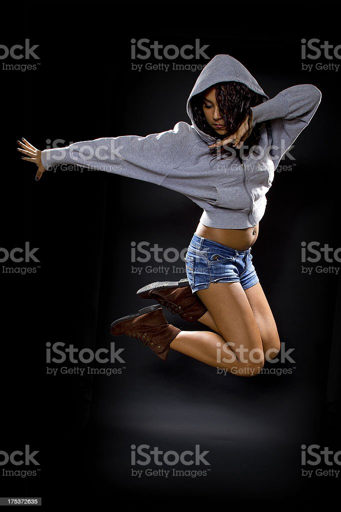 Latina Female Dancer Wearing a Hoodie Jumping royalty-free stock photo