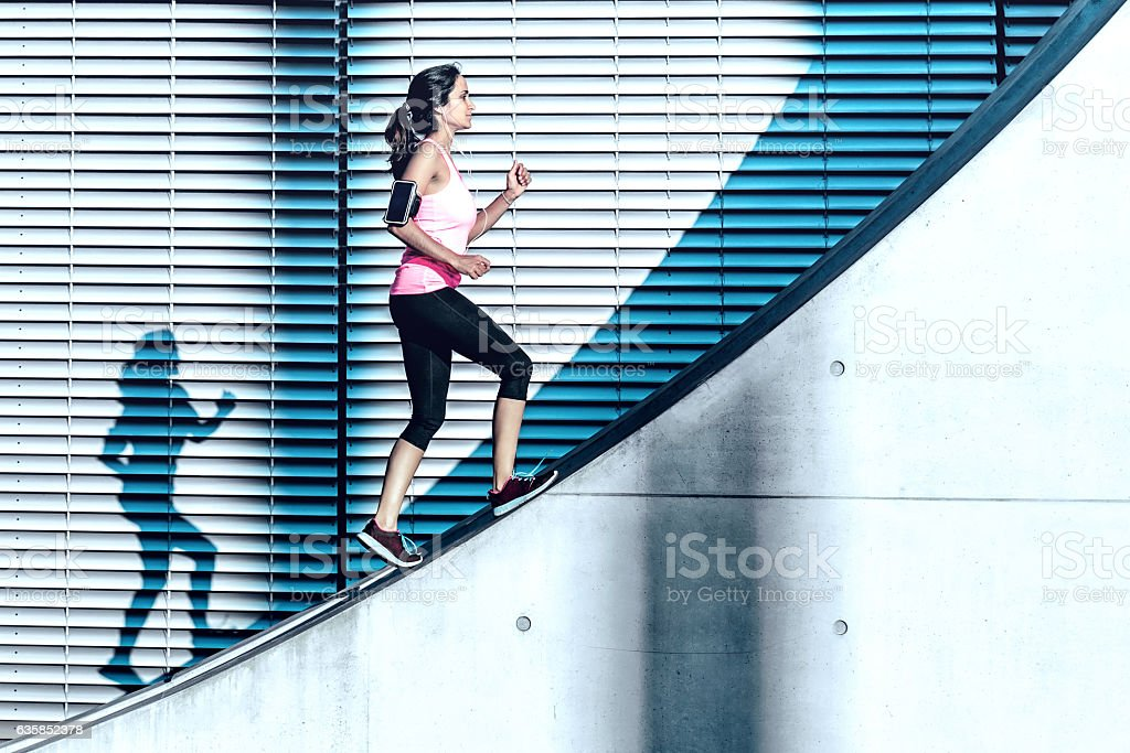 latina sports woman running up on concrete wall in berlin stock photo
