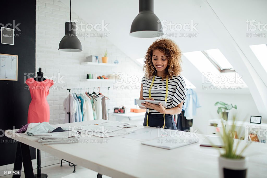 Latina Tailor Using DIgital Tablet In Her Workshop stock photo