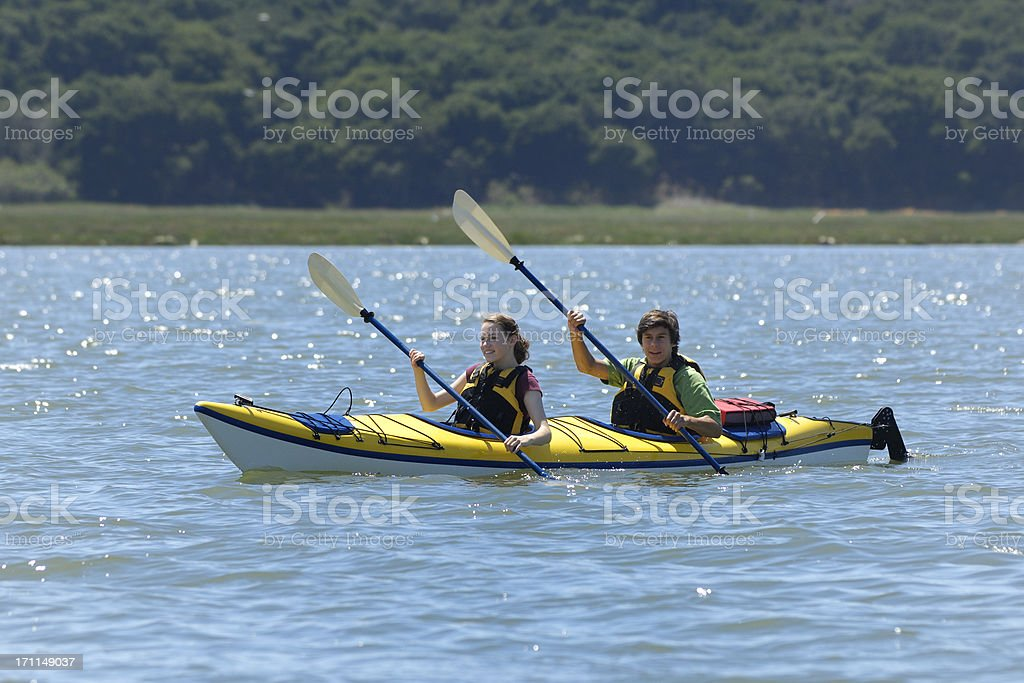 Latino and Caucasian Teenagers Kayaking on Body of Water royalty-free stock photo
