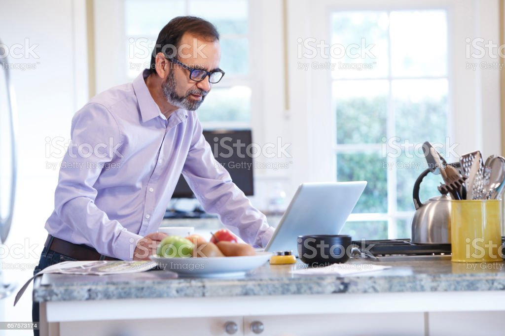 Latino Businessman Working From Home At His Kitchen Counter stock photo