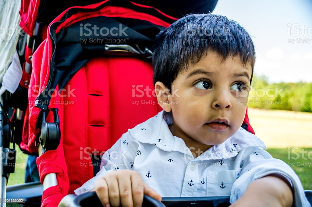 Latino child in a stroller stock photo
