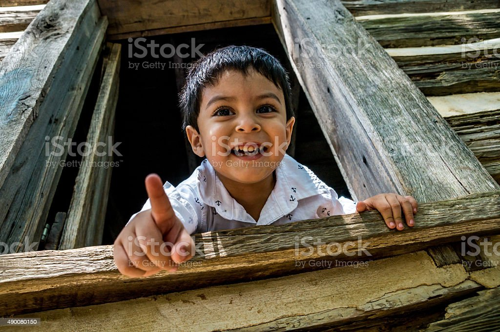 Latino child looking out a window stock photo