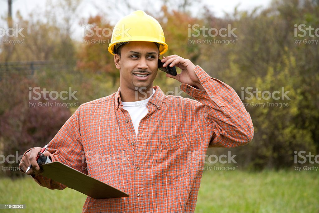 latino construction worker smiling on cell phone royalty-free stock photo
