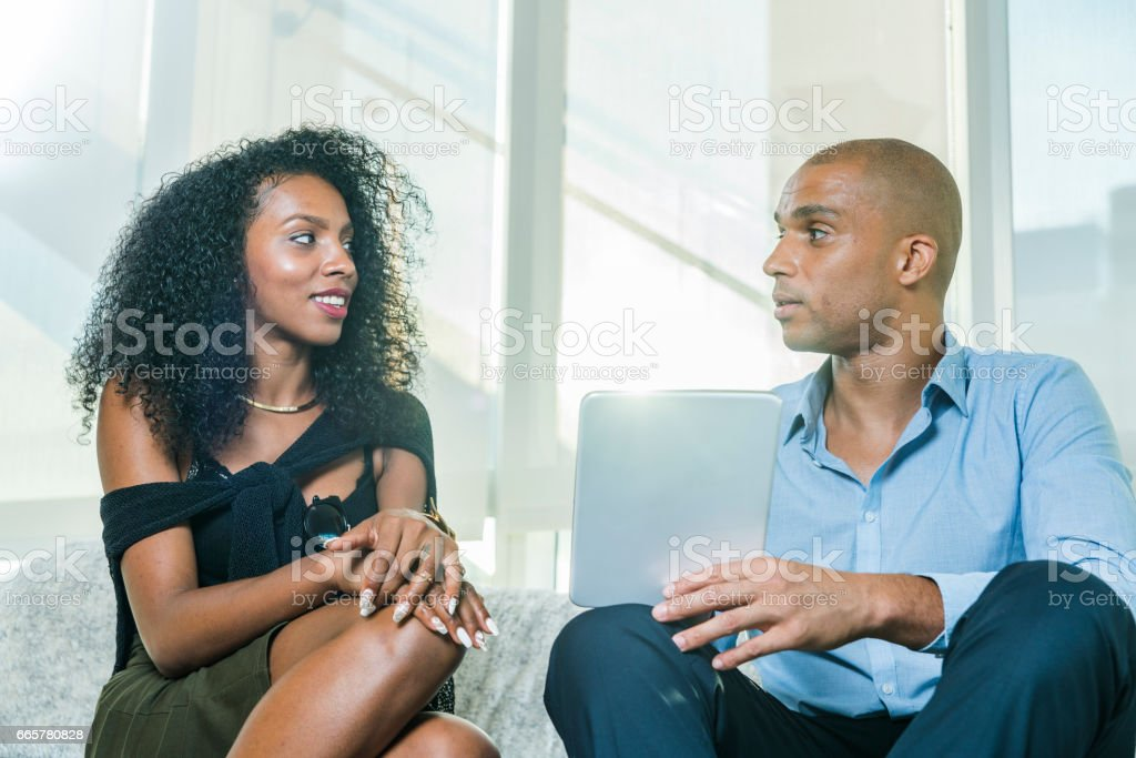 Latino couple with tablet  talking about business and stock photo
