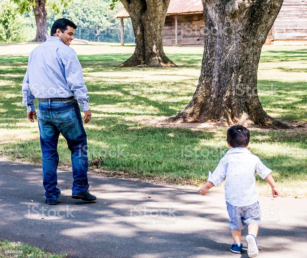 Latino father and child walking outside stock photo