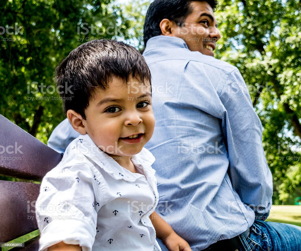 Latino father and son sitting outside stock photo