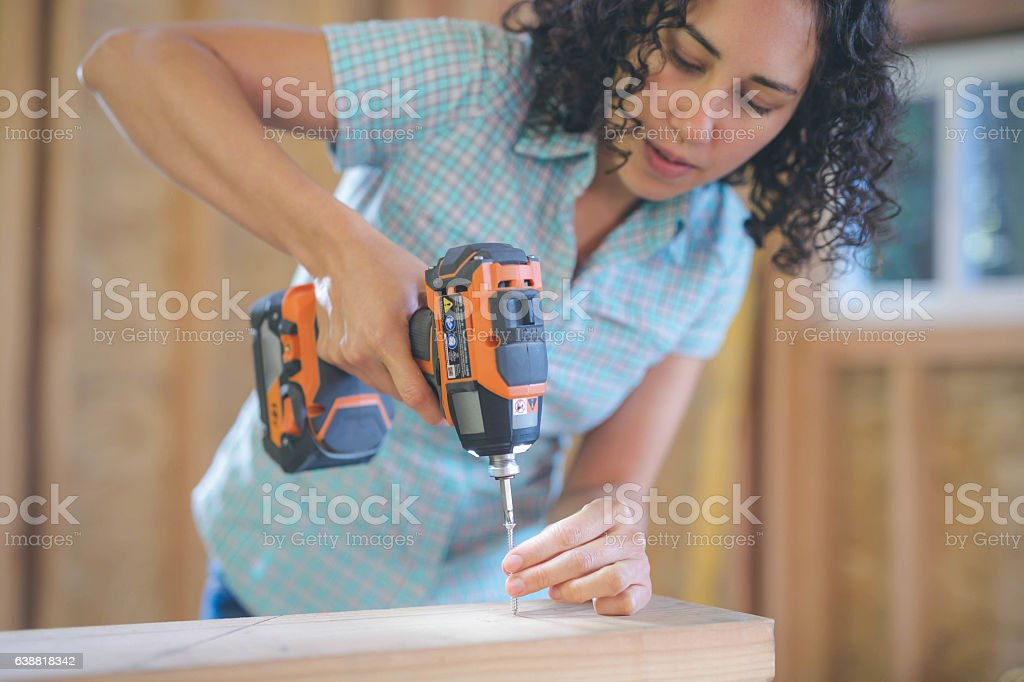 Latino female using a cordless drill to drill screw stock photo