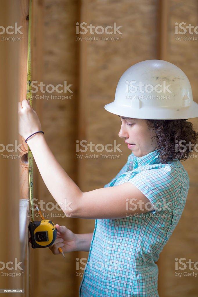 Latino female using a tape measure to check window stock photo