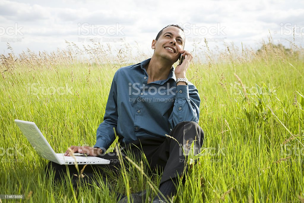 Latino male on laptop and phone royalty-free stock photo