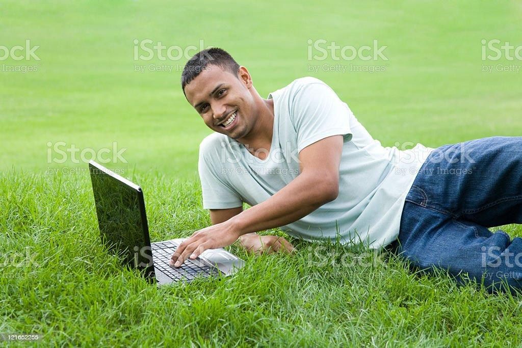latino male typing using a wireless laptop royalty-free stock photo