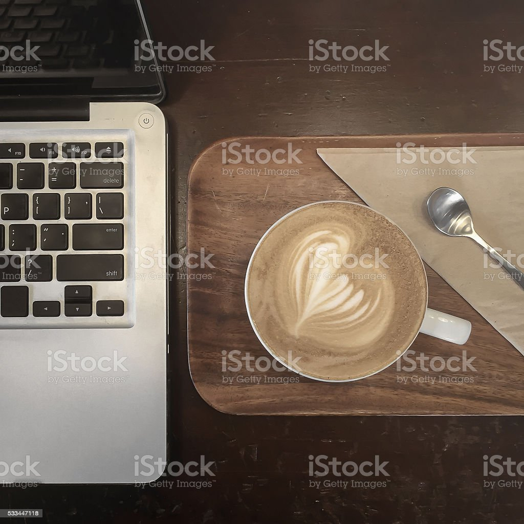Latte art coffee and Laptop computer stock photo
