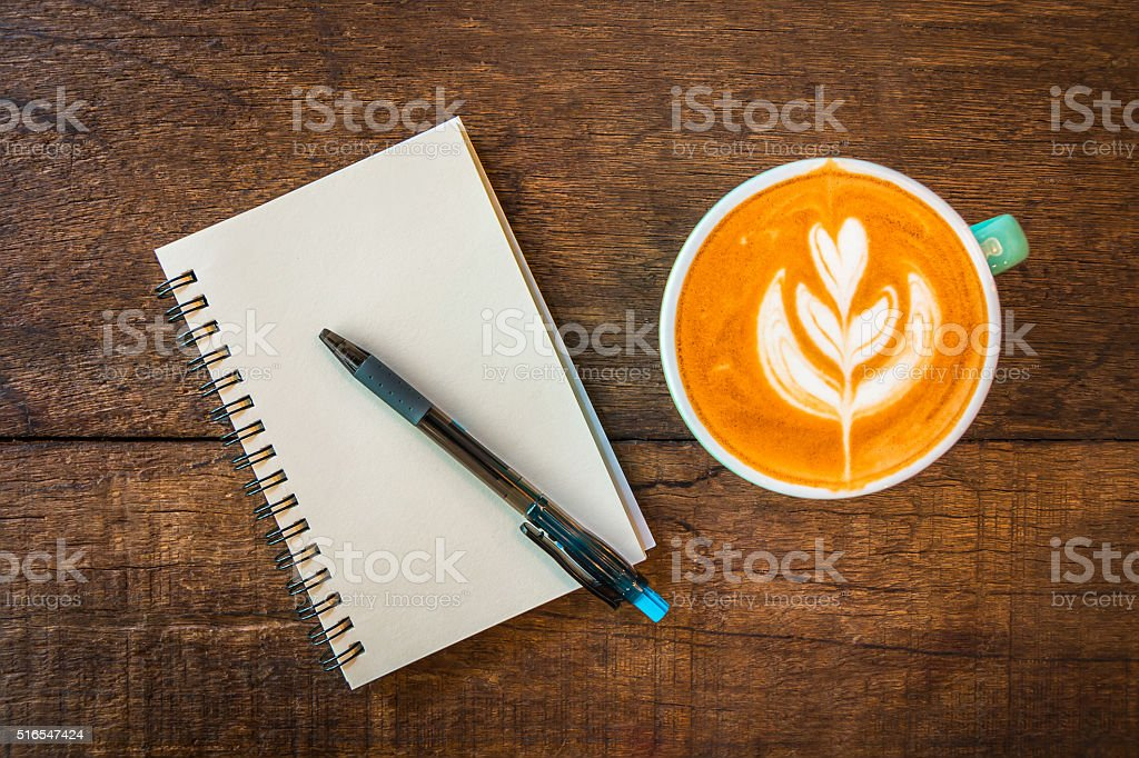 Latte hot coffee in green cup and blank note book. stock photo