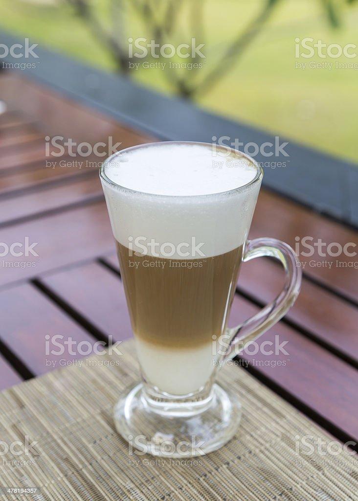 Latte macchiato in a glass with milk froth stock photo