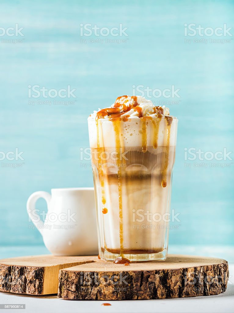 Latte macchiato with whipped cream and caramel sauce in tall stock photo