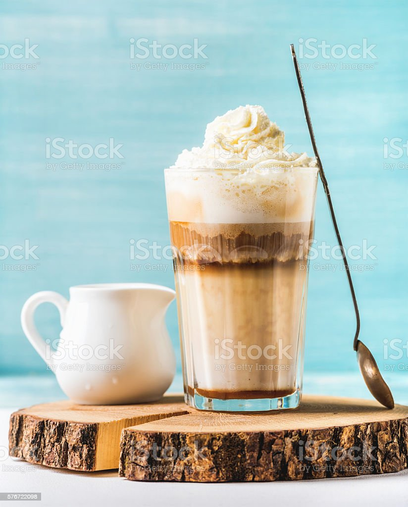 Latte macchiato with whipped cream, serving silver spoon and white stock photo
