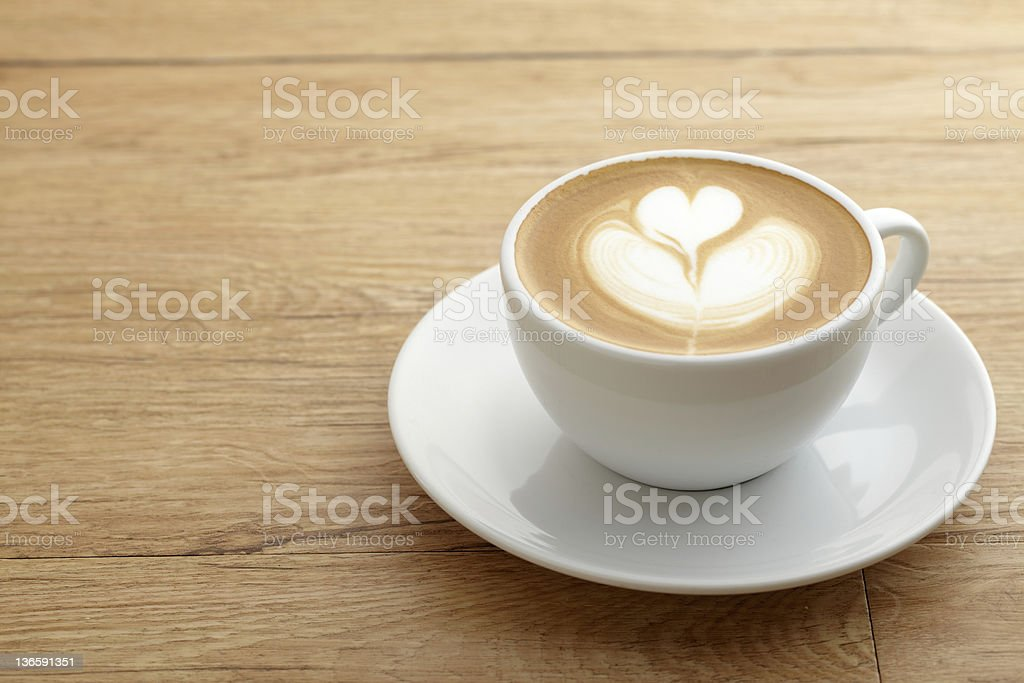 A latte with foam art forming a heart on a saucer on a table royalty-free stock photo
