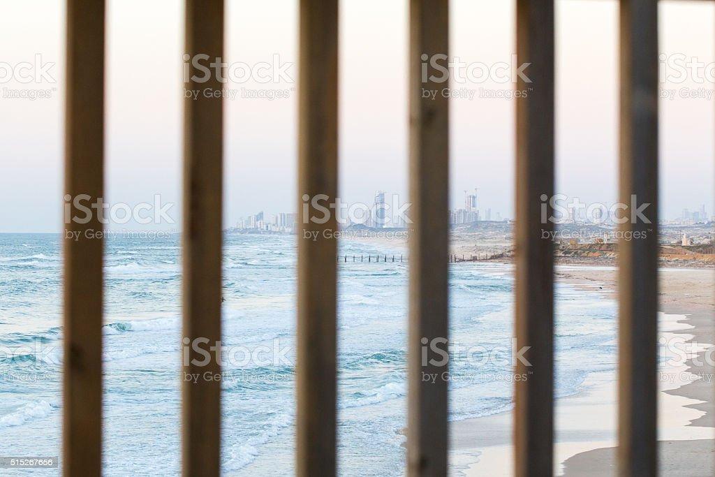 Lattice grid city buildings sea shore wooden fence view, sunset. stock photo