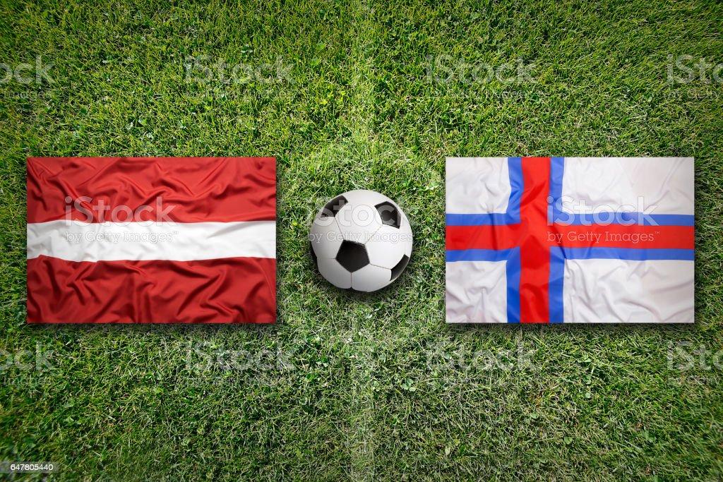 Latvia and Faroe islands flags on soccer field stock photo