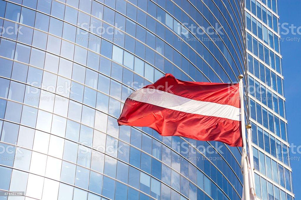 Latvia flag against glass skyscraper royalty-free stock photo