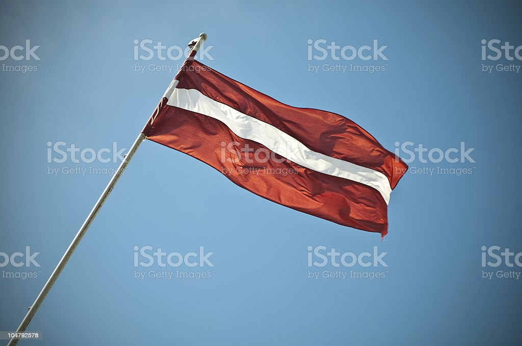 Latvian national flag banding/waving in the sky. stock photo