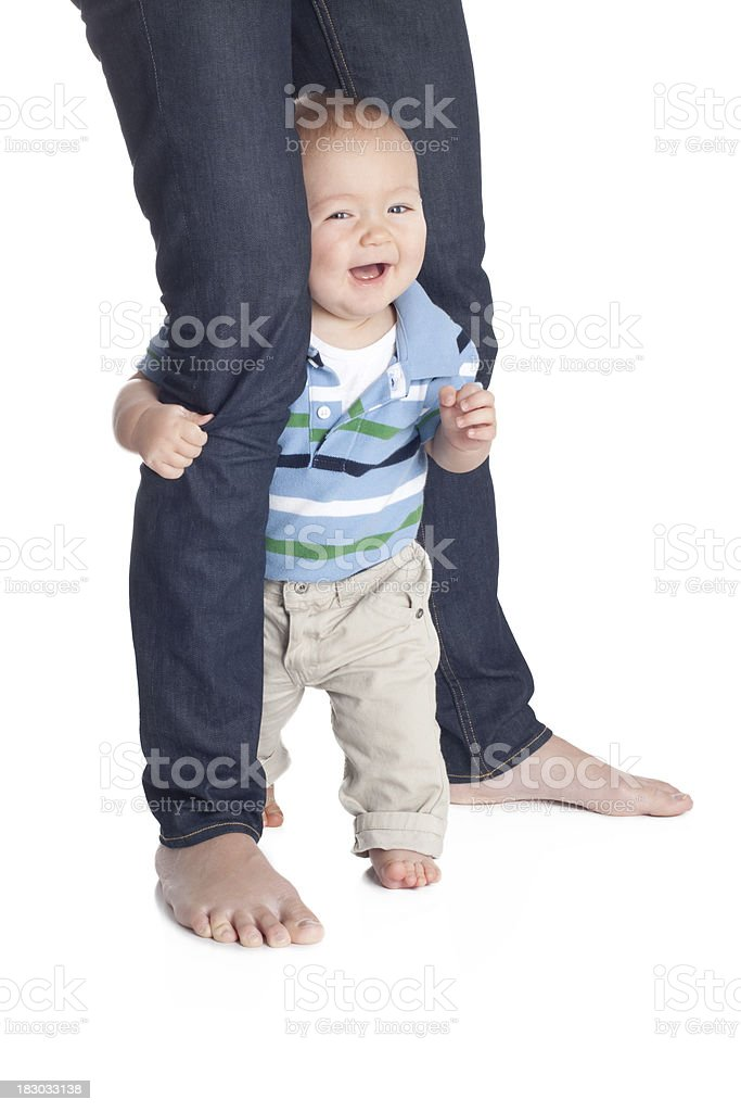 Laughing 7 Month Old Baby Holding Onto Parent Leg royalty-free stock photo