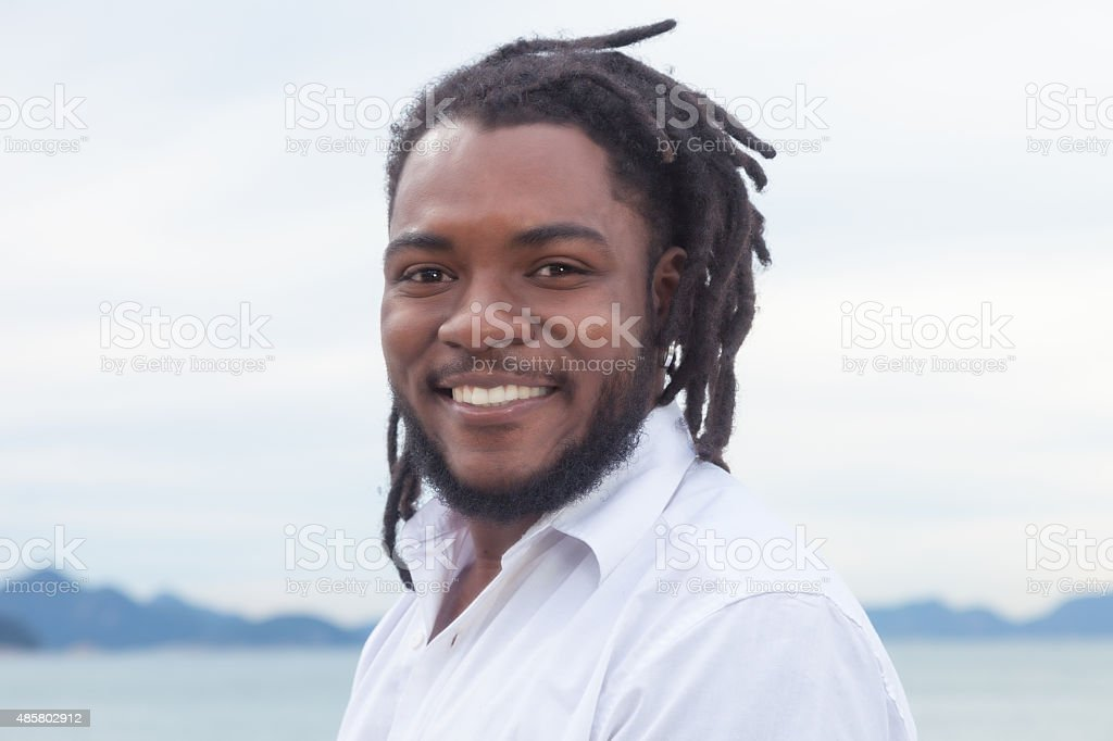 Laughing african american guy with dreadlocks and white shirt stock photo