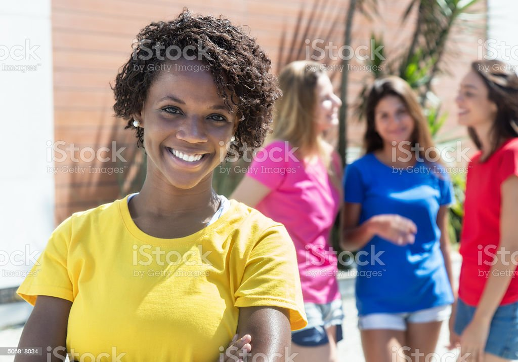 Laughing african woman with three girlfriends in the city stock photo
