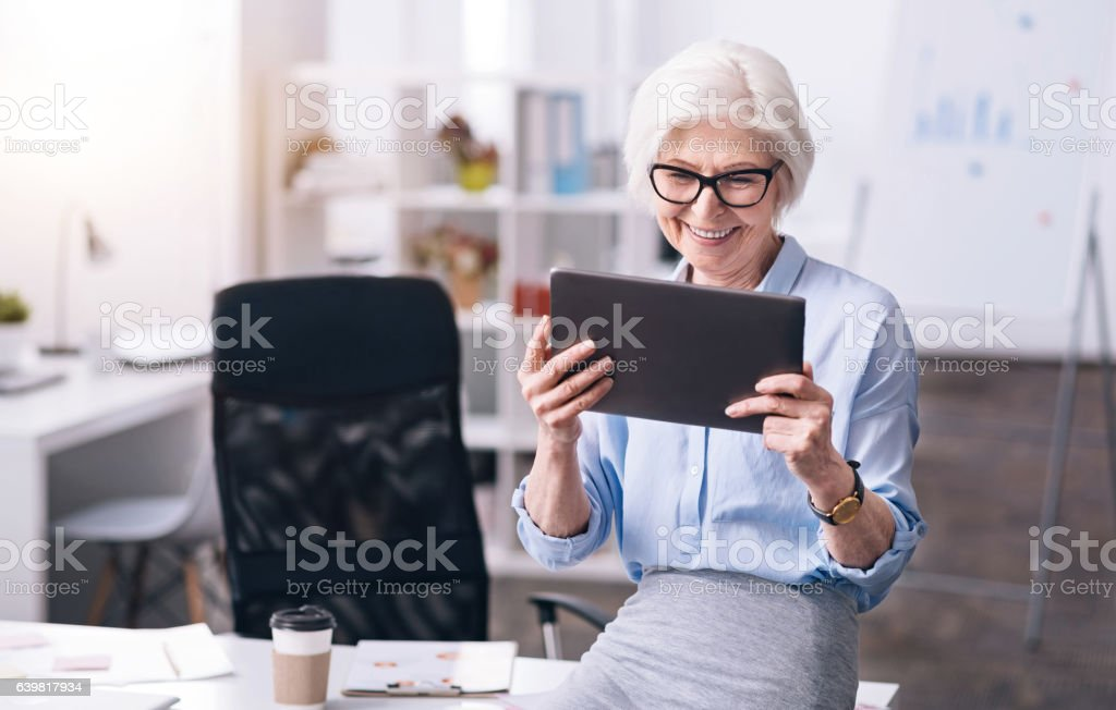 Laughing aged woman enjoying her job in the office stock photo