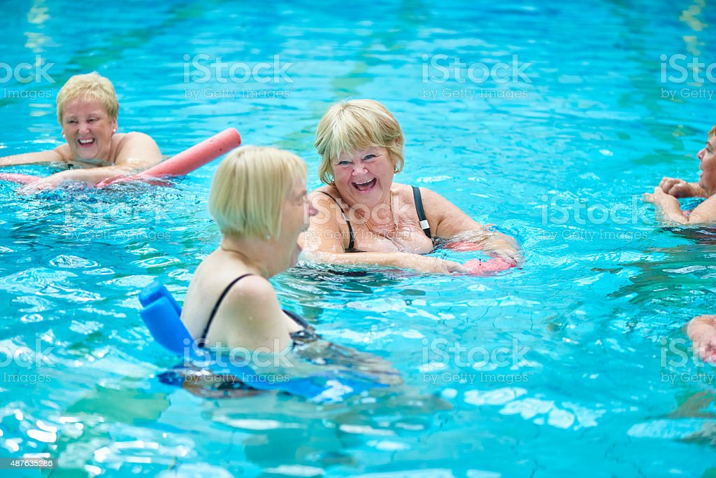 laughing and joking senior water aerobics stock photo
