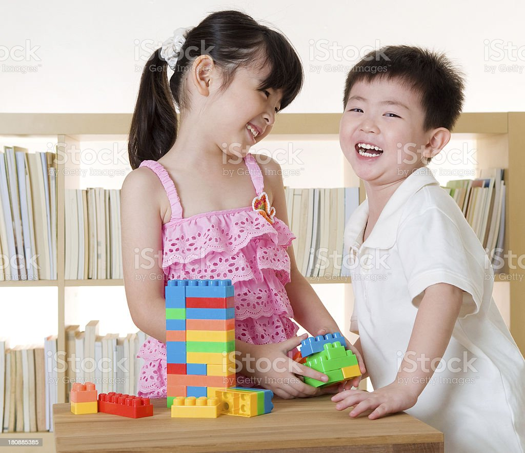 Laughing Asian toddlers playing with blocks stock photo