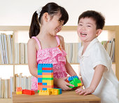 Laughing Asian toddlers playing with blocks