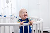 Laughing baby boy standing in bed
