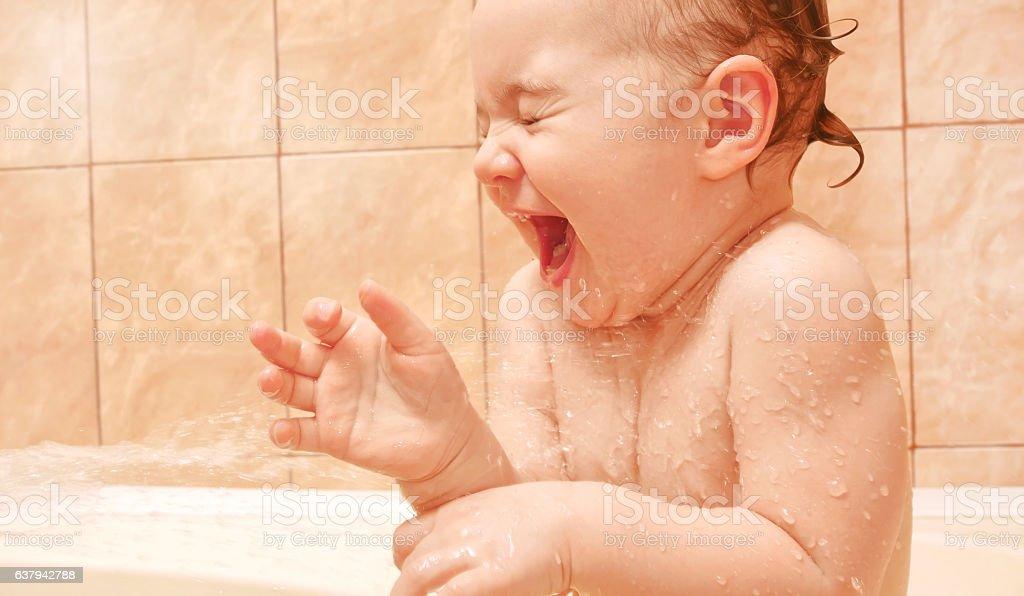 Laughing baby girl having fun washing in bath. stock photo