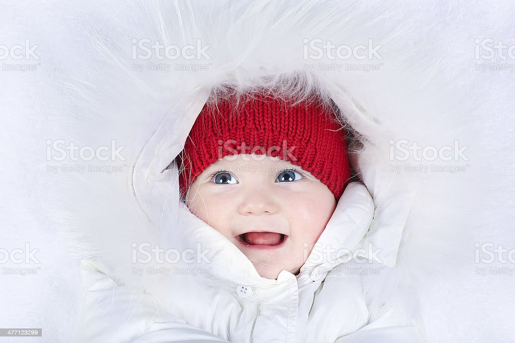 Laughing baby with beautiful blue eyes in white snow suit royalty-free stock photo