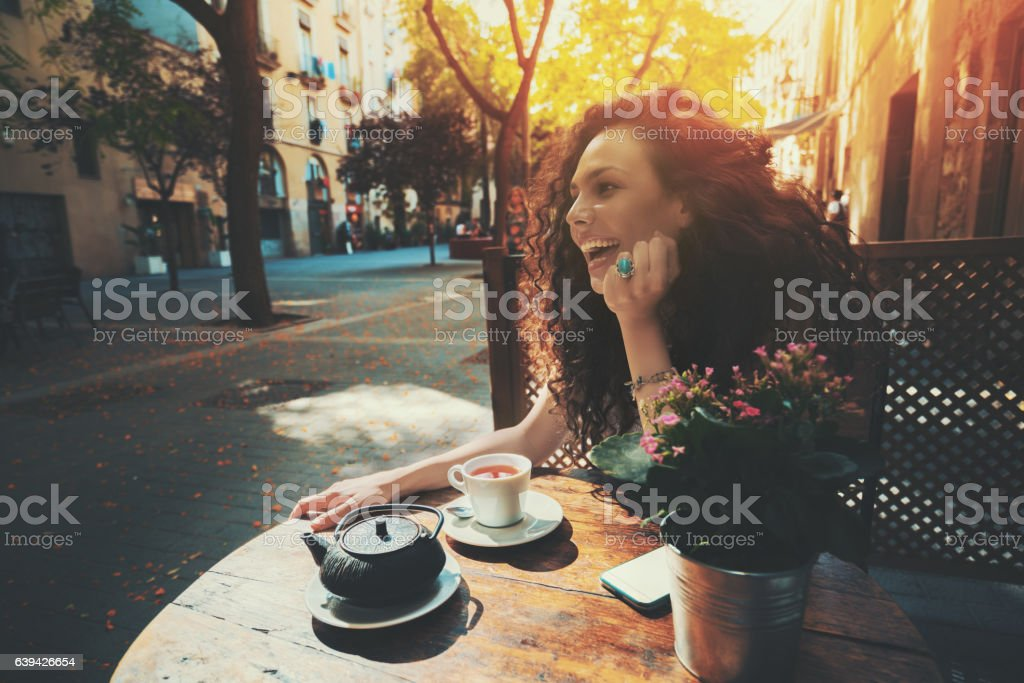 Laughing beautiful curly girl in cafe stock photo