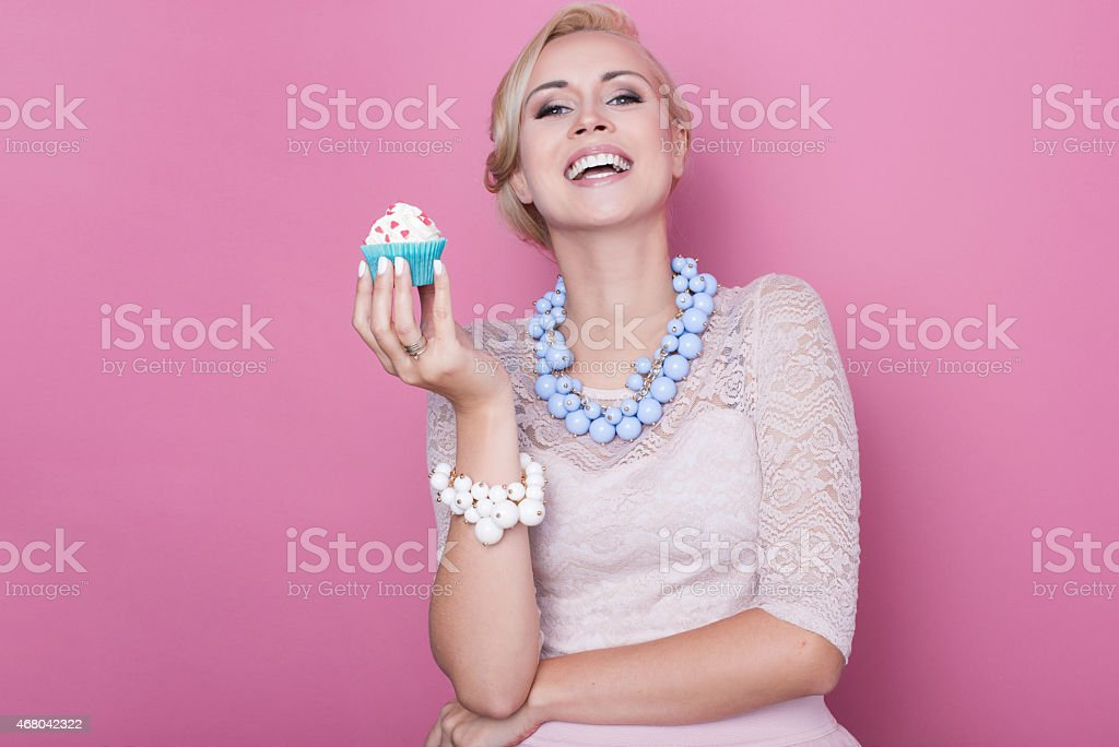 Laughing beautiful women hold little colorful cake. Soft colors stock photo