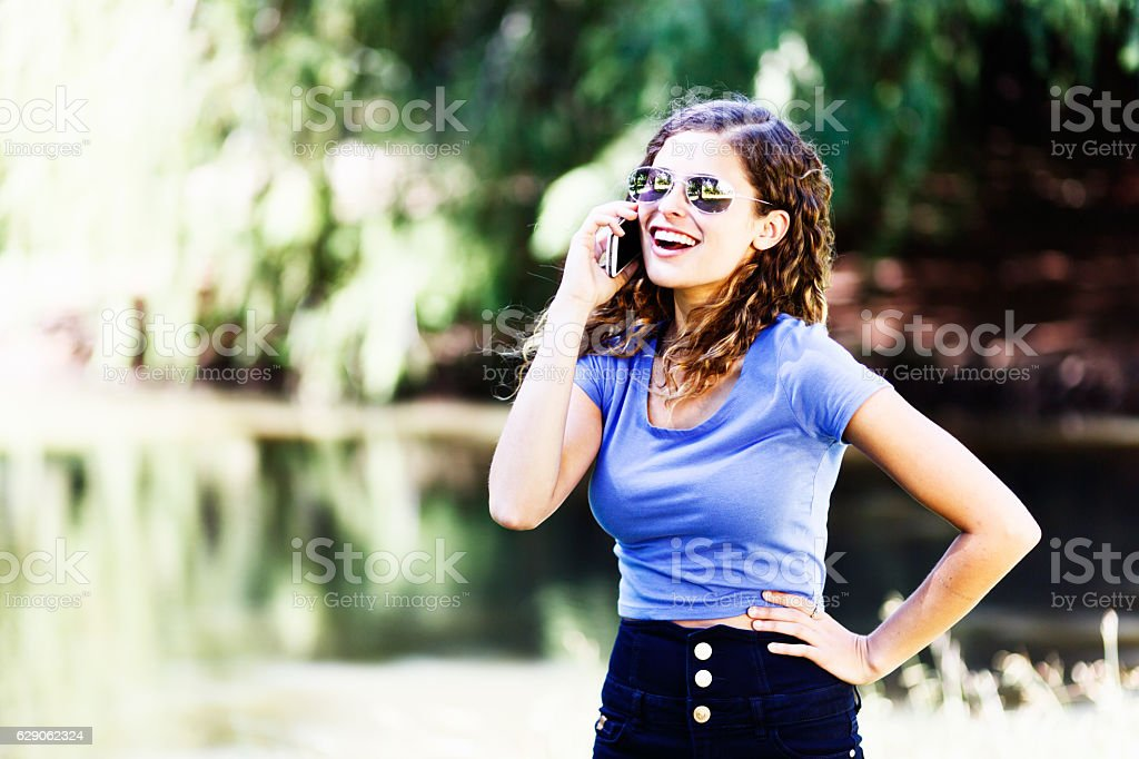 Laughing beauty with cellphone stands by idyllic lake in sunshine stock photo