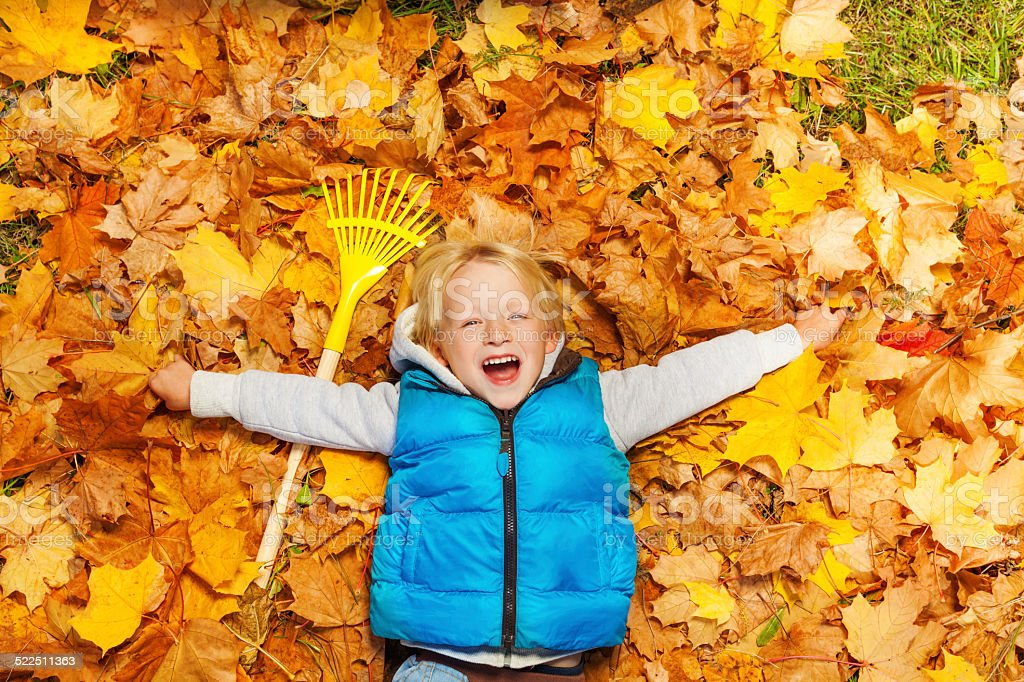 Laughing boy laying on the autumn leaves with rake stock photo