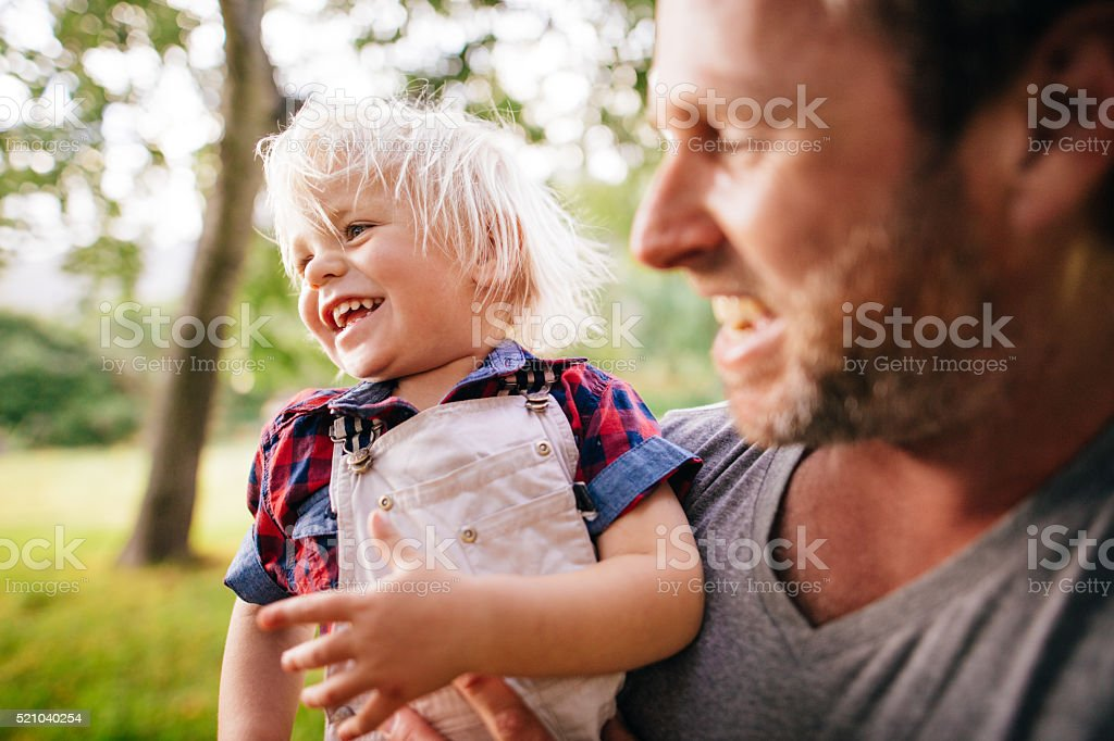 Laughing boy receives cuddles from his lovely father at park stock photo