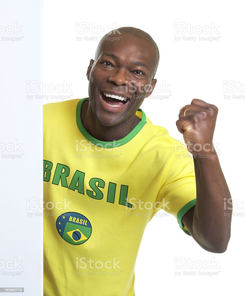Laughing brazilian soccer fan behind a signboard stock photo