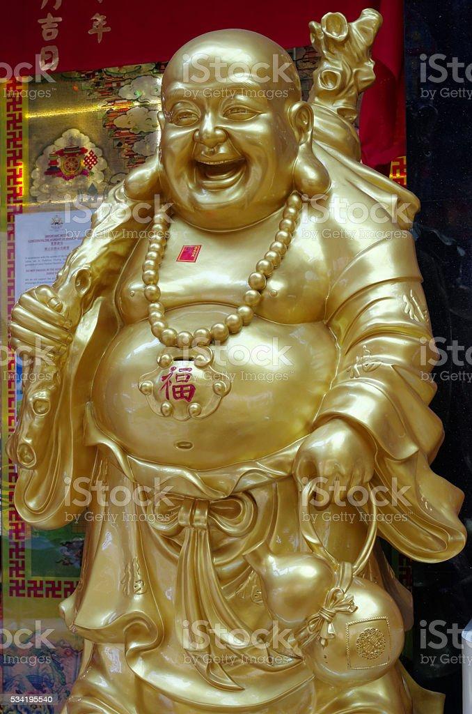 laughing buddha statue in thekchen choling stock photo