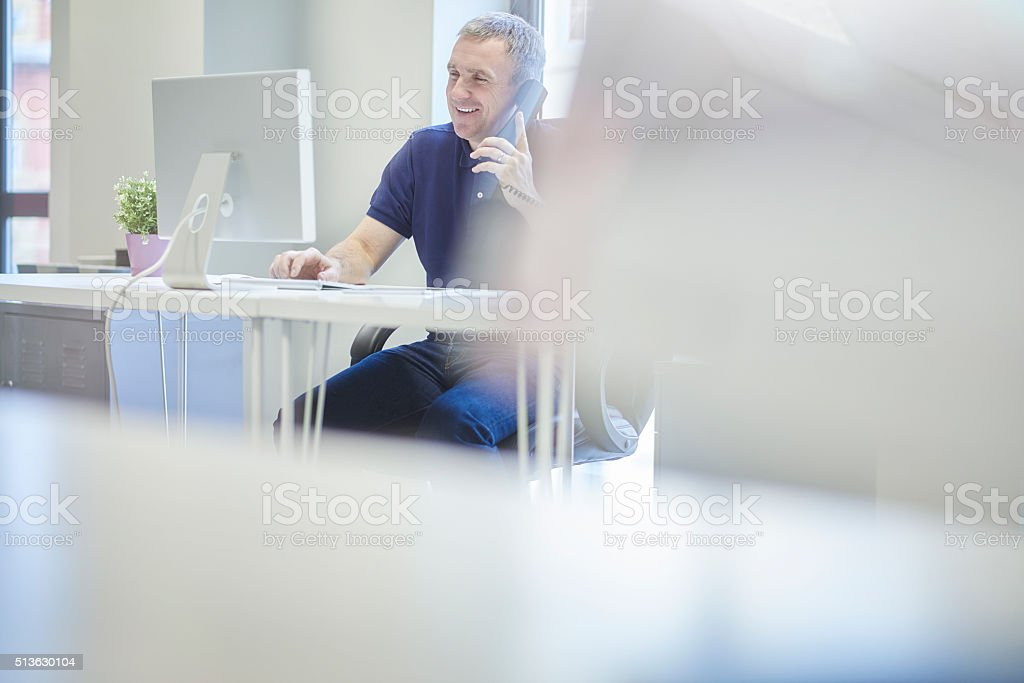 laughing business owner on the phone. stock photo