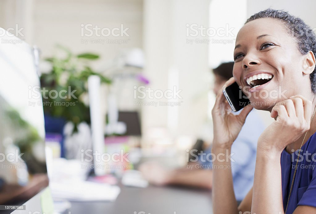 Laughing businesswoman talking on cell phone in office stock photo